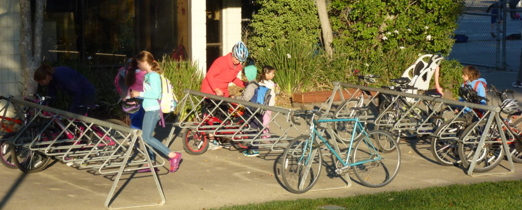 Students locking up their bicycles as they arrive at school.