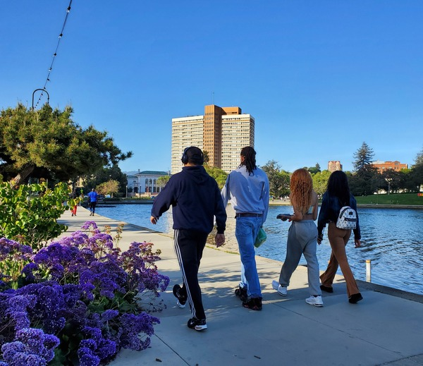 A group of four people walks on a trail by Lake Merritt in Oakland.