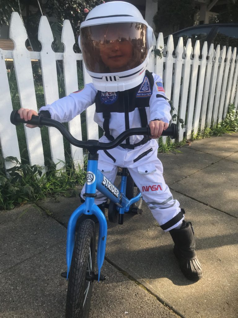 Child on bike in space suit